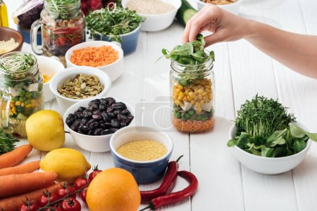 Photo for Cropped view of woman cooking salad in glass gar on wooden white table - Royalty Free Image
