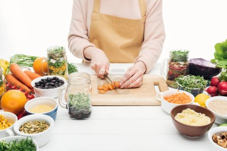 cropped view of woman in apron cutting carrots on wooden table isolated on white
