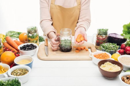 cropped view of woman in apron adding sliced carrot at jar with salad on wooden table isolated on white