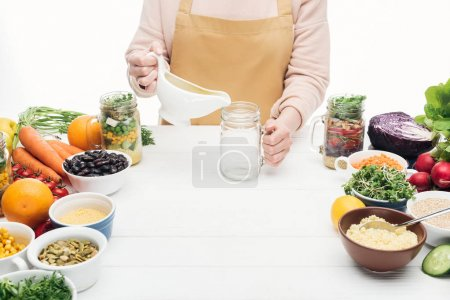 Photo for Cropped view of woman in apron adding oil in empty glass on wooden table isolated on white - Royalty Free Image