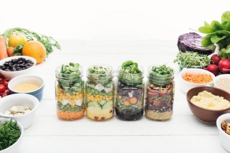 Photo for Vegetable salad in glass jars on wooden white table isolated on white - Royalty Free Image