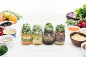 "Постер, картина, фотообои ""vegetable salad in glass jars on wooden white table isolated on white"""