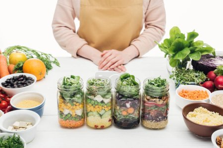 Photo for Partial view of woman in apron standing near glass jars with salad on wooden table isolated on white - Royalty Free Image