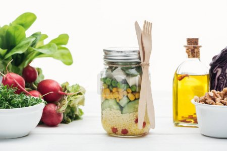 Photo for Fresh vegetable salad in glass jar near oil and radish isolated on white - Royalty Free Image