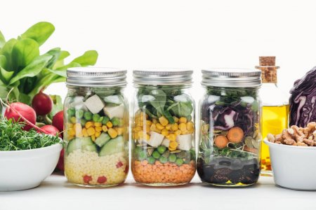 Photo for Fresh vegetable salad in glass jars near oil and radish isolated on white - Royalty Free Image