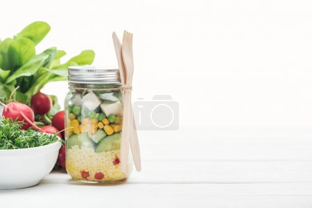 Photo for Fresh vegetable salad in glass jar near radish isolated on white - Royalty Free Image