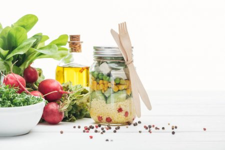 Photo for Fresh vegetable salad in glass jar near oil, radish and spices isolated on white - Royalty Free Image