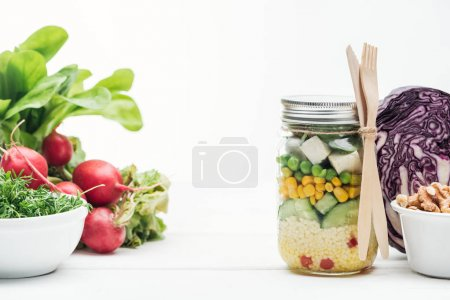 Photo for Fresh vegetable salad in glass jar near radish, red cabbage and nuts isolated on white - Royalty Free Image