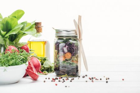Photo for Fresh vegetable salad in glass jar near spices and radish isolated on white - Royalty Free Image