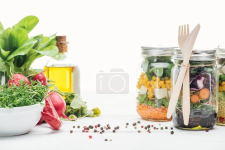 Photo for Fresh vegetable salad in glass jars with wooden cutlery isolated on white - Royalty Free Image