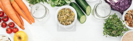 Photo for Top view of tasty fruits and vegetables in bowls near glass jars on wooden white table with copy space, panoramic shot - Royalty Free Image
