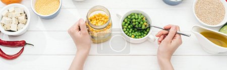 Foto de Cropped view of woman adding green peas in jar with salad on wooden white table, panoramic shot - Imagen libre de derechos