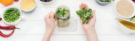 Foto de Vista recortada de la mujer añadiendo hojas verdes en frasco con ensalada en mesa blanca de madera, tiro panorámico - Imagen libre de derechos