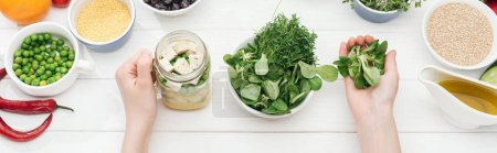 Photo for Cropped view of woman adding greens in jar with tofu cheese on wooden white table, panoramic shot - Royalty Free Image