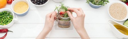 Photo for Cropped view of woman adding green sprouts in jar with salad on wooden white table, panoramic shot - Royalty Free Image