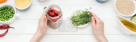 Photo for Cropped view of woman holding jar with salad and green sprouts on wooden white table , panoramic shot - Royalty Free Image