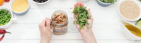 Photo for Cropped view of woman adding sprouts in jar with nuts on wooden white table , panoramic shot - Royalty Free Image
