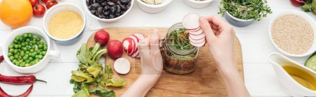 Photo for Cropped view of woman adding radish slices in jar with salad on wooden white table, panoramic shot - Royalty Free Image