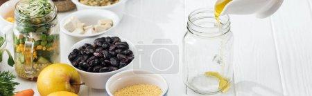 Photo pour Vue recadrée de femme versant l'huile dans le pot en verre vide sur la table blanche en bois, projectile panoramique - image libre de droit