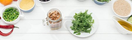 Photo for Top view of glass jar with nuts near plate with green arugula on wooden white table, panoramic shot - Royalty Free Image
