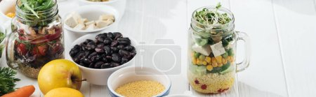 Photo for Ingredients in bowl near glass jars with salad on wooden white table, panoramic shot - Royalty Free Image