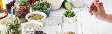 Photo for Cropped view of woman adding green peas in glass jar on wooden white table, panoramic shot - Royalty Free Image