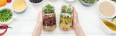 Photo for Cropped view of woman holding jars with tasty salad on wooden white table , panoramic shot - Royalty Free Image