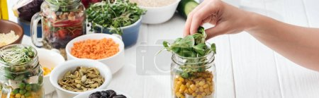 Photo for Cropped view of woman adding greens in glass jar on wooden white table, panoramic shot - Royalty Free Image