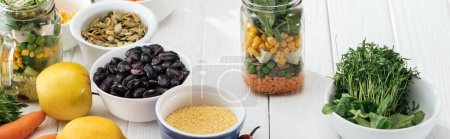 Photo for Greens in bowl near fruits and vegetables in glass jar on wooden white table, panoramic shot - Royalty Free Image
