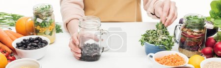 Photo for Cropped view of woman in apron adding greens to glass jar with beans on wooden table isolated on white, panoramic shot - Royalty Free Image