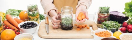 Photo for Cropped view of woman in apron adding carrot slices to glass jar with beans on wooden table isolated on white, panoramic shot - Royalty Free Image