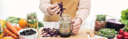 Photo for Cropped view of woman in apron adding red cabbage in glass jar on wooden table isolated on white, panoramic shot - Royalty Free Image