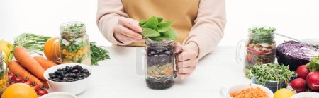 Photo for Partial view of woman in apron holding glass jar with salad and green leaves on wooden table isolated on white, panoramic shot - Royalty Free Image
