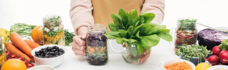 Photo for Cropped view of woman in apron holding glass jar with salad and green leaves on wooden table isolated on white, panoramic shot - Royalty Free Image