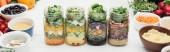 """Постер, картина, фотообои """"свежий овощной салат в стеклянных банках на деревянном белом столе, изолированном на белом панорамном снимке"""""""