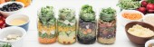 "Постер, картина, фотообои ""delicious vegetable salad in glass jars on wooden white table isolated on white, panoramic shot"""