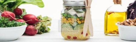 Photo pour Plan panoramique de salade de légumes frais dans un bocal en verre près de l'huile et radis isolé sur blanc - image libre de droit