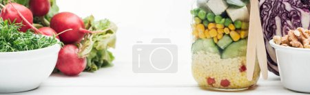 Photo for Fresh vegetable salad in glass jar near radish, red cabbage and nuts isolated on white, panoramic shot - Royalty Free Image