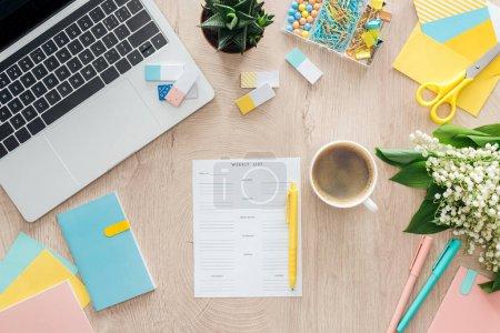 Photo pour Vue du dessus de la liste hebdomadaire, tasse de café, papeterie, ordinateur portable et fleurs sur table en bois - image libre de droit