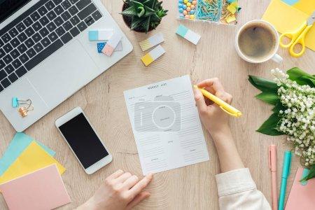 Photo pour Vue recadrée de la femme tenant stylo sur la liste hebdomadaire, travaillant sur une table en bois avec tasse de café, papeterie, ordinateur portable et fleurs - image libre de droit