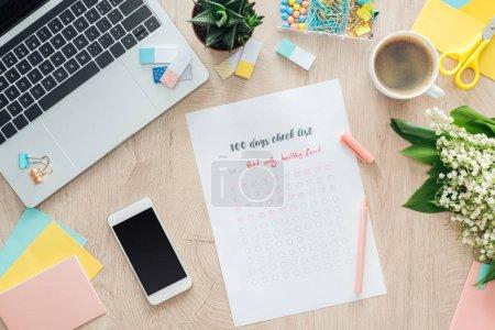 Photo pour Vue du dessus de 100 jours check list, papeterie et ordinateur portable avec smartphone sur table en bois - image libre de droit