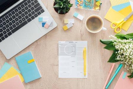 Photo pour Vue du dessus de la liste hebdomadaire, papeterie, tasse de café et ordinateur portable sur table en bois - image libre de droit