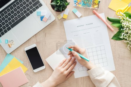 Photo for Cropped view of woman sitting behind wooden table with smartphone, laptop and stationery, writing in monthly planner - Royalty Free Image