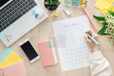 Photo for Cropped view of woman sitting behind wooden table with smartphone, laptop and stationery, writing notes in monthly planner - Royalty Free Image
