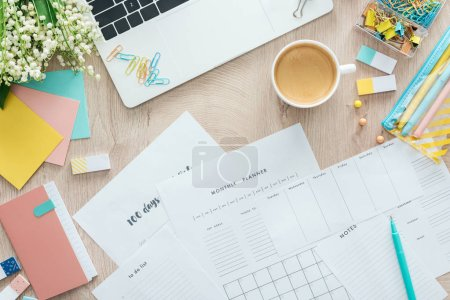 Photo for Top view of planners, stationery, cup of coffee and laptop on wooden table - Royalty Free Image