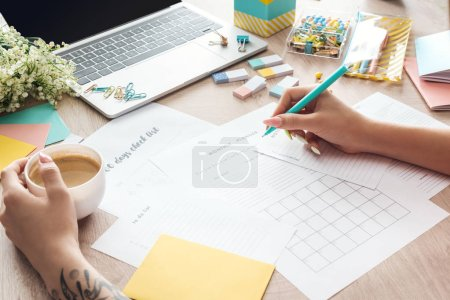 Photo for Cropped view of woman sitting with cup of coffee behind wooden table with stationery and laptop and writing in notes planners - Royalty Free Image