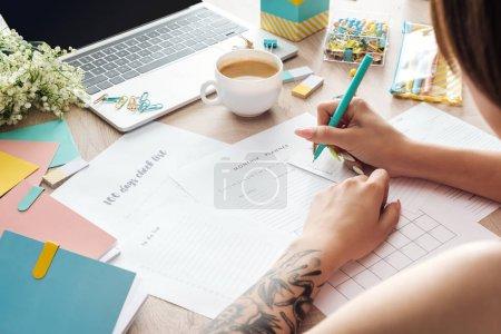 Photo pour Vue recadrée de la femme assise derrière une table en bois avec ordinateur portable et papeterie, écriture dans des planificateurs de papier - image libre de droit