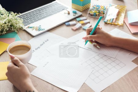 Photo for Cropped view of woman holding cup of coffee in hand, sitting behind wooden table with laptop and stationery, writing in paper planners - Royalty Free Image