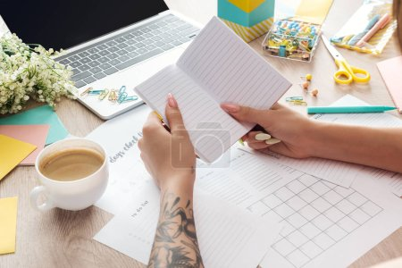 Photo for Cropped view of woman holding notepad in hands, working behind wooden table with cup of coffee, stationery, laptop and flowers - Royalty Free Image