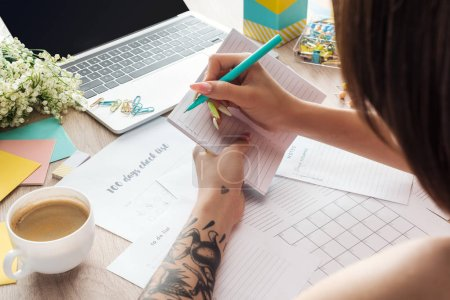 Photo pour Vue recadrée de femme écrivant des notes dans le bloc-notes, s'asseyant derrière la table en bois avec l'ordinateur portatif, les planificateurs et la papeterie - image libre de droit